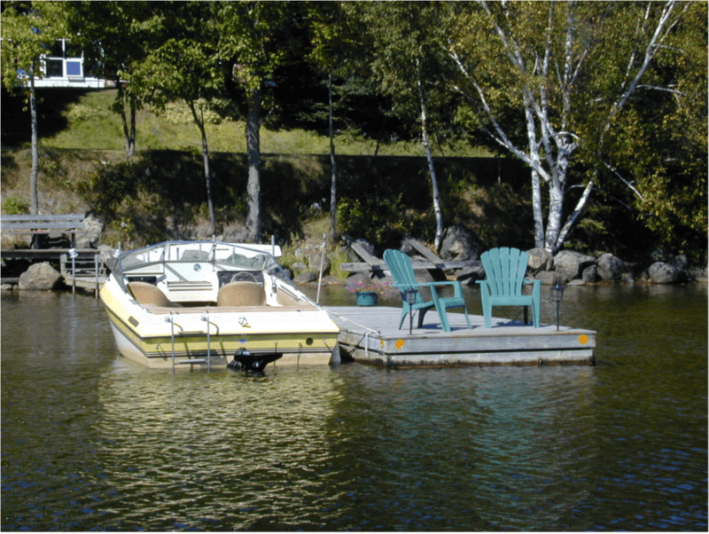 A boat in water next to a dock