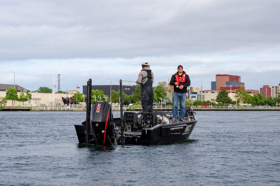 Steve and Tyler salmon fishing in front of the Sault Ste. Marie sky line