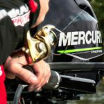 Fishing line on a spinning reel set against a Mercury outboard motor
